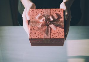 Hands holding out wrapped gift