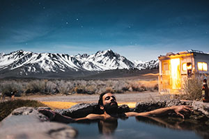 Man relaxing in hot tub under night sky